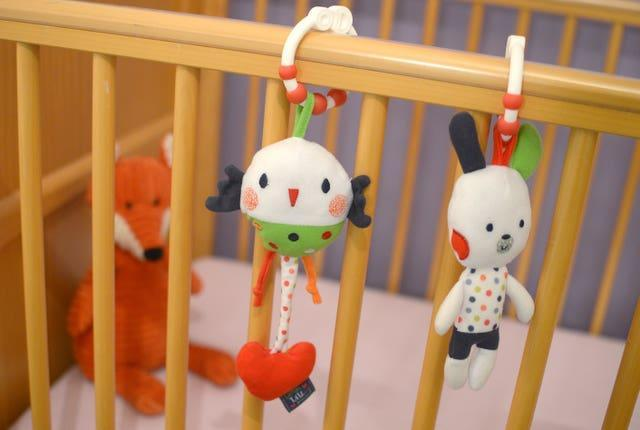 A child's soft toys hang on the side of a cot (Anthony Devlin/PA)