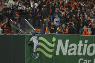 Los Angeles Dodgers left fielder AJ Pollock looks over the fence after San Francisco Giants' Kris Bryant hit a home run during the seventh inning of Game 1 of a baseball National League Division Series Friday, Oct. 8, 2021, in San Francisco. (AP Photo/John Hefti)