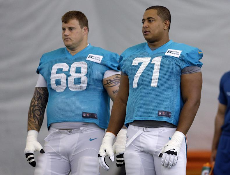 FILE - In this July 24, 2013, file photol, Miami Dolphins guard Richie Incognito (68) and tackle Jonathan Martin (71) stand on the field during NFL football practice in Davie, Fla. Martin, the offensive tackle at the center of the Dolphins' bullying scandal, has been traded to the San Francisco 49ers. The Dolphins announced the deal Tuesday night, March 11, 2014, on the first day of NFL free agency. Martin's move cross country brings him back to the Bay Area to be reunited with his former Stanford coach, Jim Harbaugh. (AP Photo/Lynne Sladky, File)