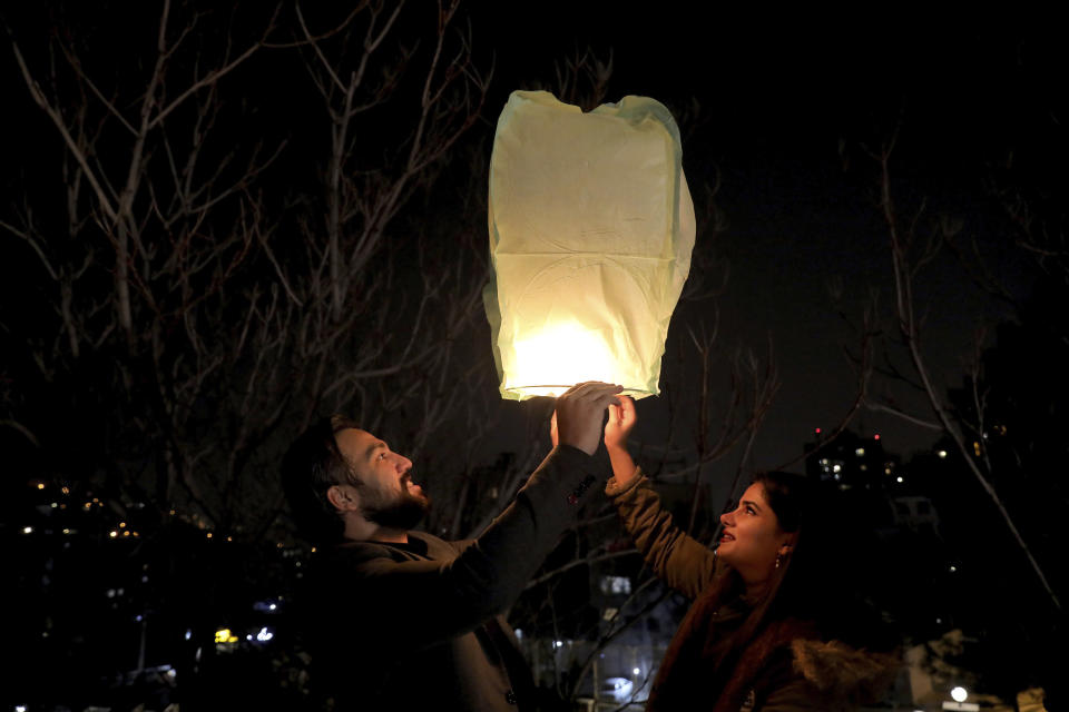 """People fly a wishing lantern ahead of the Persian New Year, or Nowruz, meaning """"New Day."""" in Tehran, Iran, Monday, March 15, 2021. (AP Photo/Ebrahim Noroozi)"""
