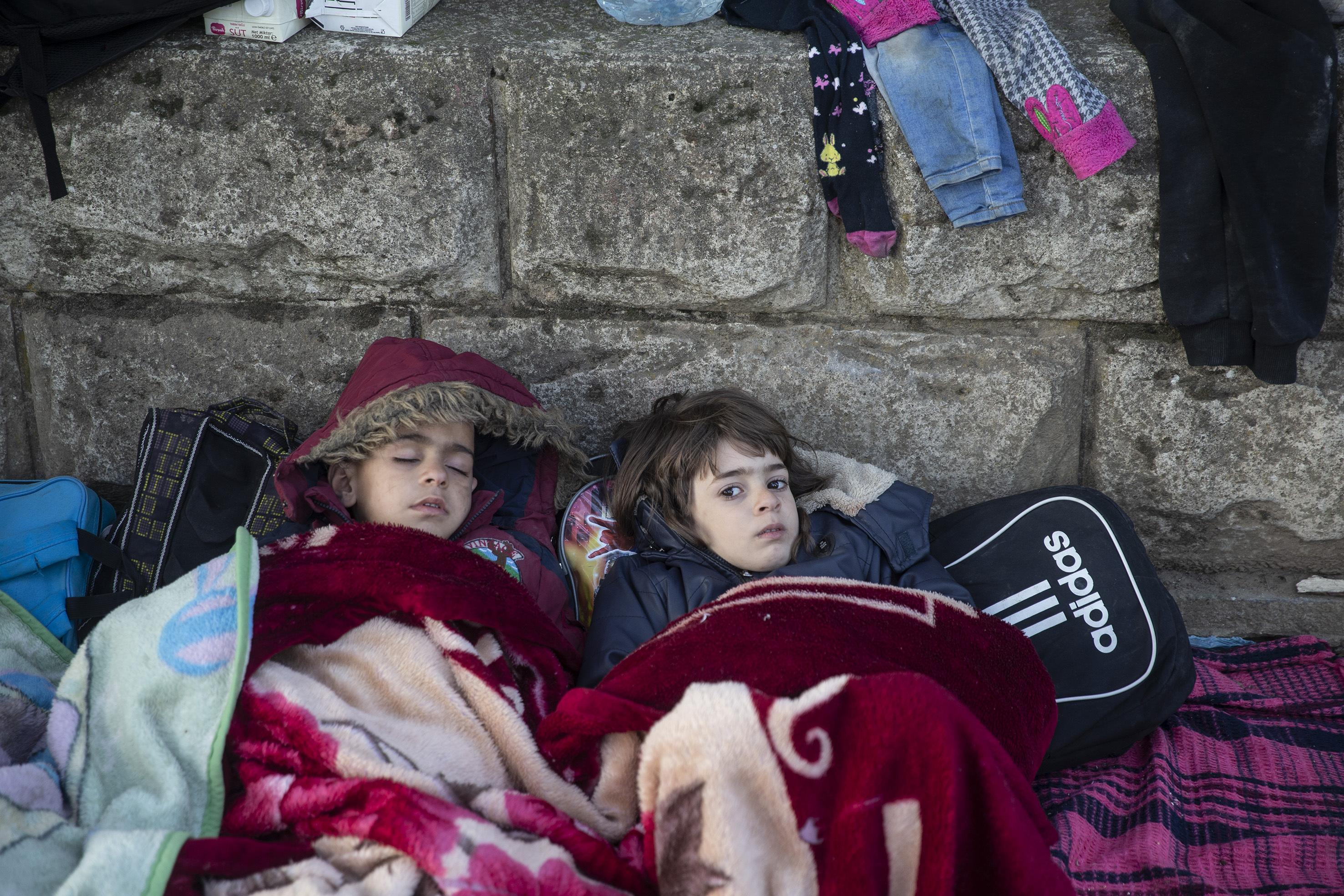 EDIRNE, TURKEY - MARCH 02: An irregular migrant child wakes up beside a sleeping child as they continue to flock at the Pazarkule Border Gate in Karaagac neighbourhood in Edirne, Turkey to reach Greece on March 02, 2020. The number of irregular migrants leaving Turkey for Europe has reached 117,677 on Monday, Turkish Interior Minister Suleyman Soylu said on Twitter. The migrants are leaving Turkey through northwestern Edirne province bordering Greece and Bulgaria. Thousands of migrants flocked to Edirne's Pazarkule border crossing to Greece after Turkish officials announced Friday they would no longer try to stop irregular migrants from reaching Europe (Photo by Gokhan Balci/Anadolu Agency via Getty Images)