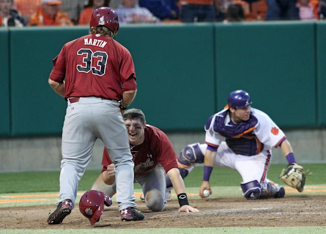 South Carolina's Grayson Greiner, center, celebrates with teammate Kyle Martin after diving around Clemson catcher Chris Okey, right, to score the tying run in an NCAA college baseball game on Sunday, March 2, 2014, in Clemson, S.C. (AP Photo/Anderson Independent-Mail, Mark Crammer)
