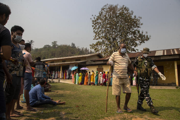 An Indian paramilitary person assists an elderly voter as people stand in queue to cast their votes in a polling station during the third phase of assembly election in Gauhati, India, Tuesday, April 6, 2021. Voters in four Indian states and a union territory are casting their ballots, in elections seen as a test for Prime Minister Narendra Modi's government which is battling the latest surge in coronavirus cases. (AP Photo/Anupam Nath)