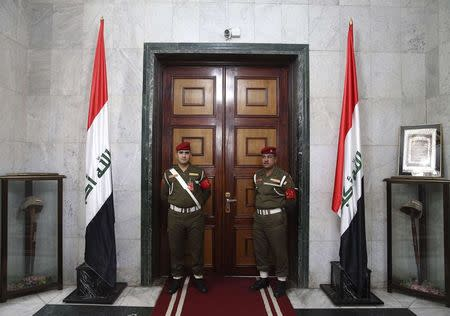 Iraqi guards stand in front of a door inside the Ministry of Defence during a visit from U.S. Secretary of Defense Chuck Hagel, in Baghdad December 9, 2014. U.S. Defense Secretary Chuck Hagel arrived in Baghdad on Tuesday as the United States expands its presence and touts progress against Islamic State militants four months after starting a campaign of air strikes in Iraq.  REUTERS/Mark Wilson/Pool (IRAQ - Tags: POLITICS MILITARY)