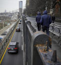 Visitors walk along Brooklyn Heights Promenade while traffic travels beneath the park, Friday April 5, 2019, in New York. The promenade makes up the top deck overhang of a deteriorating Brooklyn-Queens Expressway and the city's plans for repairs has drawn neighborhood protest, since it calls for a temporary six lane highway on the promenade. (AP Photo/Bebeto Matthews)