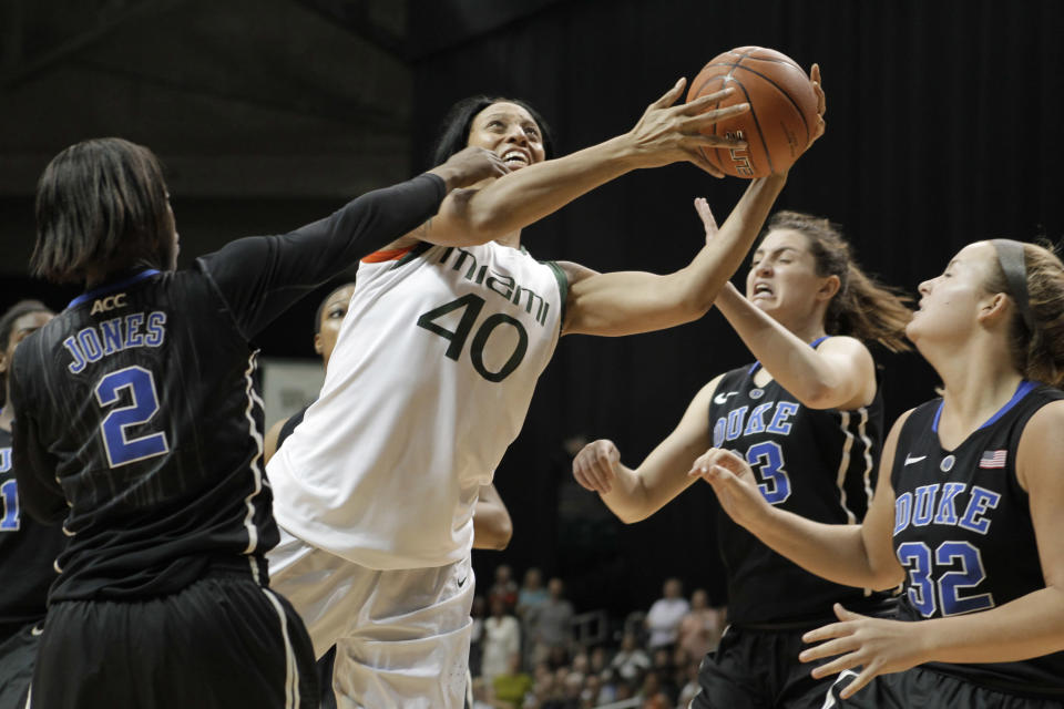 Miami's Shawnice Wilson (40) shoots as Duke's Alexis Jones (2), Haley Peters, center, and Tricia Liston (32) defend during the first half of an NCAA college basketball game in Coral Gables, Fla., Thursday, Feb. 28, 2013. (AP Photo/Luis M. Alvarez)