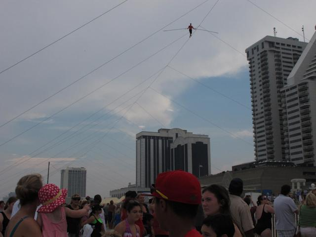 A crowd watches as daredevil Nik Wallenda walks a tightrope above the beach at Atlantic City on Thursday, Aug. 9, 2012. Officials say some 150,000 people witnessed the walk. (AP Photo/Geoff Mulvihill)
