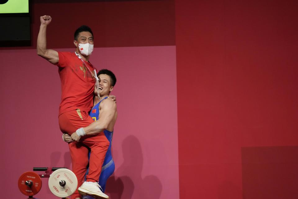 Lyu Xiaojun of China celebrates with his coach after winning the gold medal in the men's 81kg weightlifting event, at the 2020 Summer Olympics, Saturday, July 31, 2021, in Tokyo, Japan. (AP Photo/Luca Bruno)