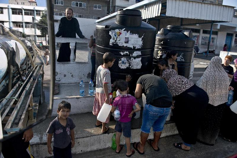 Palestinians, displaced by violence and living at a UN school in Gaza City, fill up their plastic jugs as a water supply truck makes its daily delivery on August 23, 2014 (AFP Photo/Roberto Schmidt)