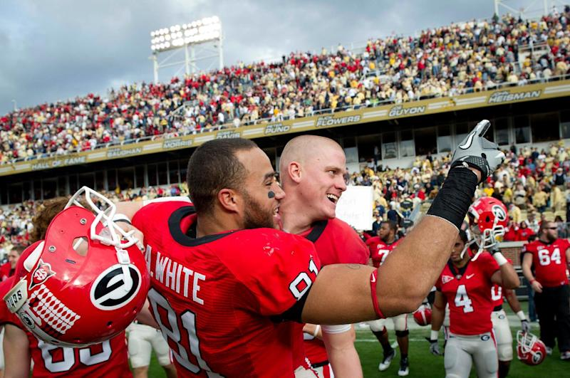 Georgia Bulldogs punter Drew Butler, right, and teammate tight end Aaron White (81) celebrate their 31-17 win over Georgia Tech in an NCAA college football game at Bobby Dodd Stadium at Historic Grant Field in Atlanta on Saturday, Nov. 26, 2011.  (AP Photo/Rich Addicks)