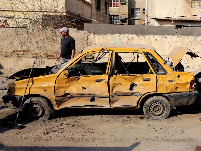 An Iraqi taxi driver inspects his damasged car after a car bomb attack near the Technology University in Sinaa Street in downtown Baghdad, Iraq, Wednesday, Jan. 15, 2014. A wave of bombings across Iraq striking busy markets and a funeral north of Baghdad killed tens of people Wednesday, authorities said, as the country remains gripped by violence after al-Qaida-linked militants took control of two cities in western Anbar province. (AP Photo/Karim Kadim)