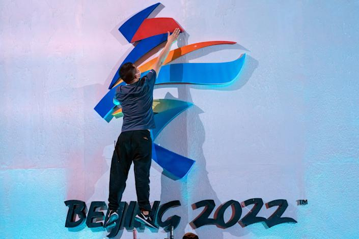 """A crew member leaps to fix a logo for the 2022 Beijing Winter Olympics before a launch ceremony to reveal the motto for the Winter Olympics and Paralympics in Beijing, Friday, Sept. 17, 2021. Organizers on Friday announced """"Together for a Shared Future"""" as the motto of the next Olympics, which is scheduled to begin on Feb. 4 of next year. (AP Photo/Mark Schiefelbein)"""