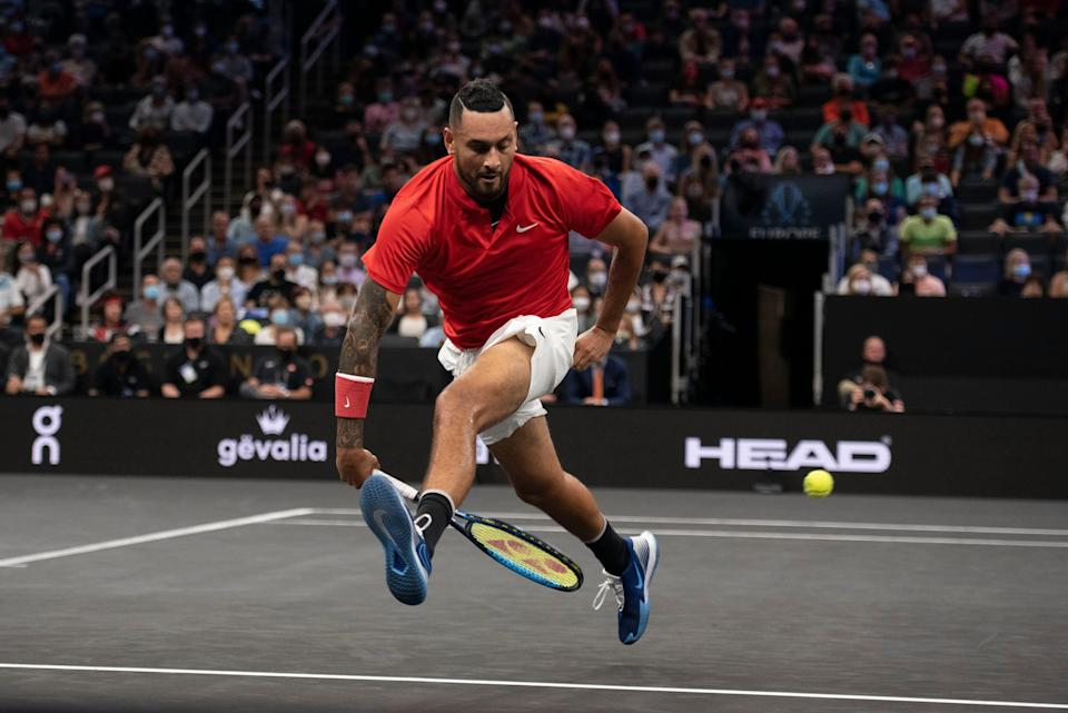 Nick Kyrgios attempts a shot between his legs during the first set of his match against Stefanos Tsitsipas at TD Garden.