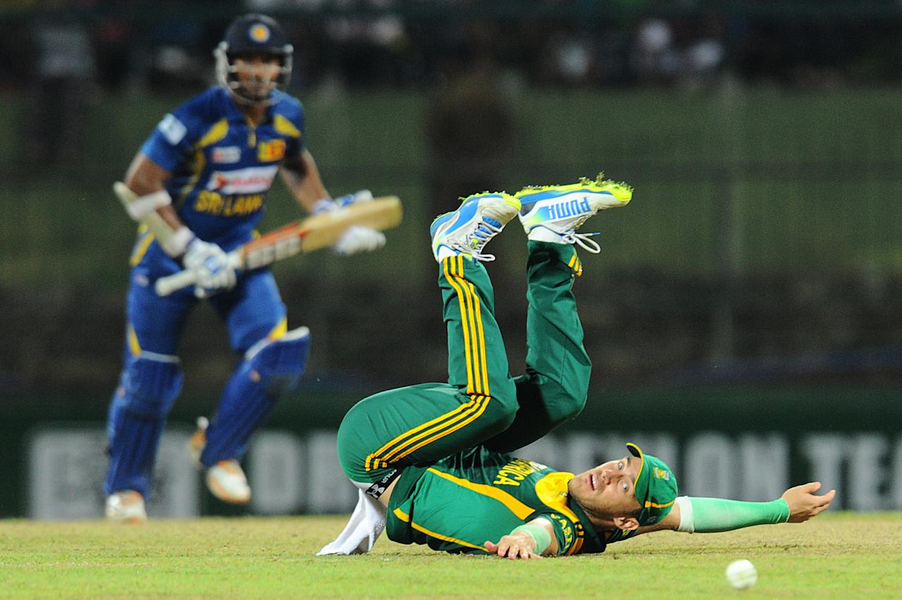 South African cricketer Faf du Plessis (R) fields a ball as Sri Lankan batsman Kumar Sangakkara looks on during the fourth One Day International (ODI) cricket match between Sri Lanka and South Africa at the Pallekele International Cricket Stadium in Pallekele on July 28, 2013. AFP PHOTO/ Ishara S.KODIKARA