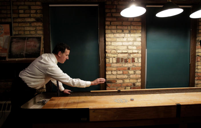 Republican presidential candidate, former Pennsylvania Sen. Rick Santorum plays shuffle board after a news conference in Green Bay, Wis., Saturday, March 24, 2012. Rick Santorum won the Louisiana Republican presidential primary Saturday, beating front-runner Mitt Romney in the race to challenge President Barack Obama. (AP Photo/Jae C. Hong)