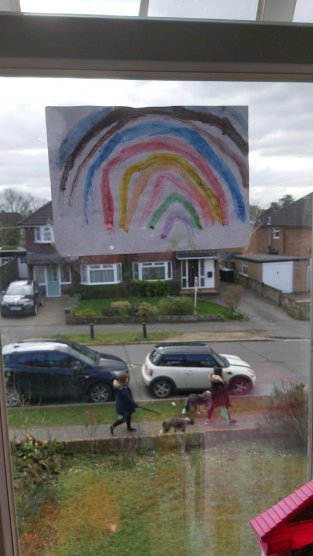 Amellie Barrett waved at friends from her bedroom. Throughout Stoke Poges village children have put rainbows in their windows.