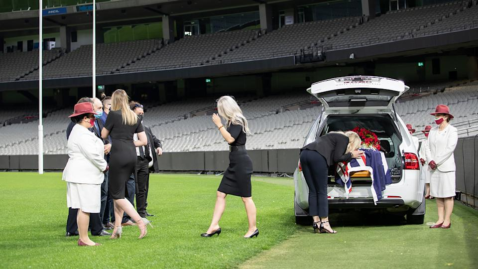 Family and friends are pictured at a service for Dean Jones at the MCG.