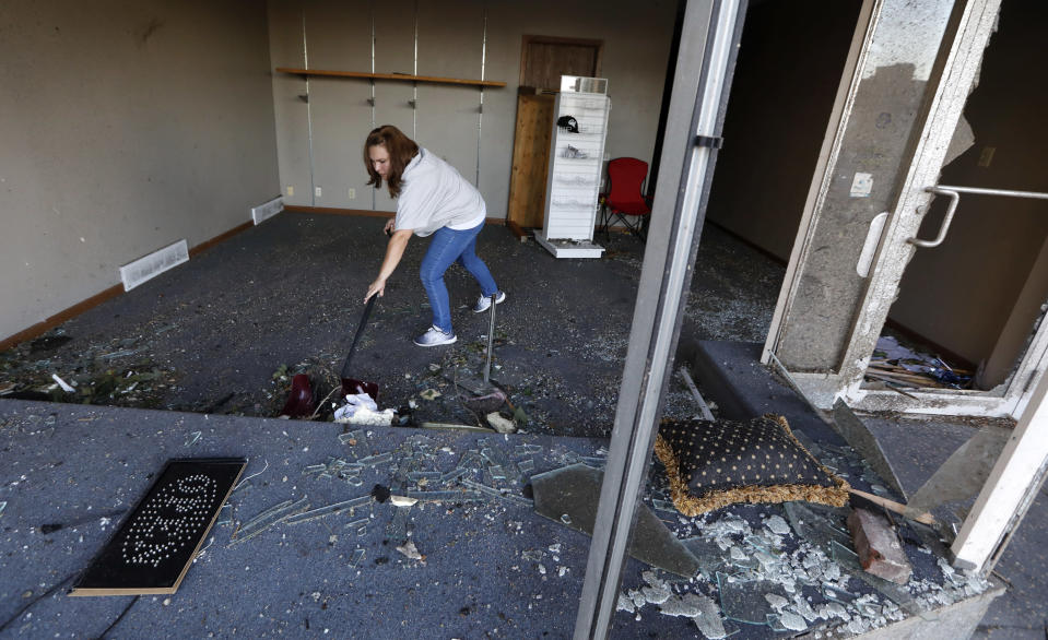 <p>Stephanie Moz, of Marshalltown, Iowa, cleans out her tornado-damaged business on Main Street, Thursday, July 19, 2018, in Marshalltown, Iowa. Several buildings were damaged by a tornado in the main business district in town including the historic courthouse. (Photo: Charlie Neibergall/AP) </p>