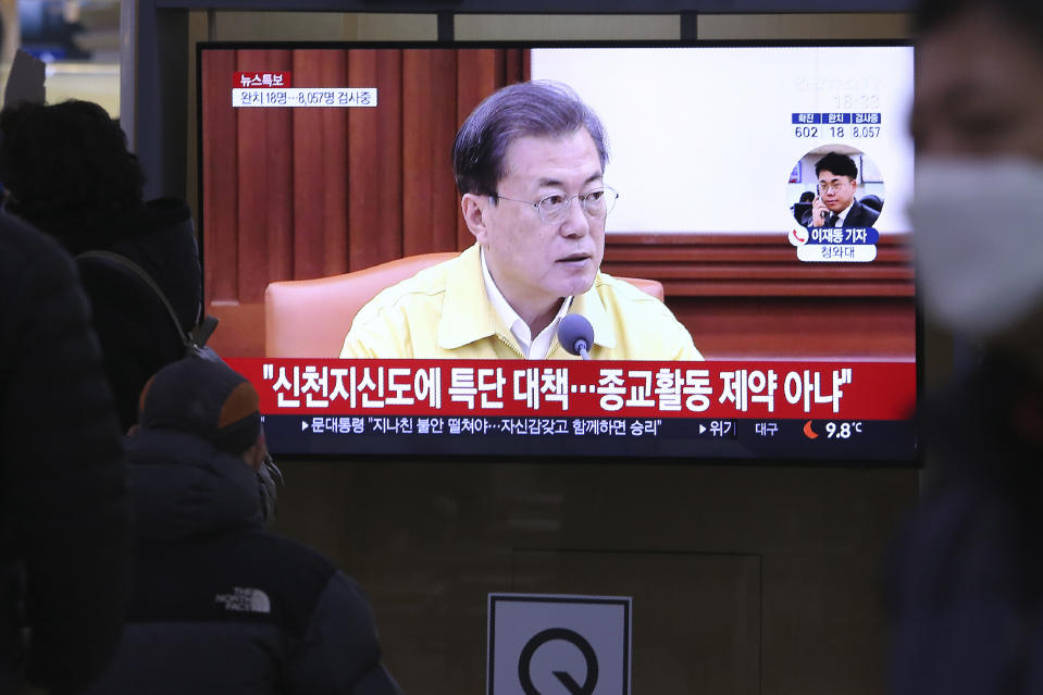 """People watch a TV screen showing South Korean President Moon Jae-in's speech during a news program at the Seoul Railway Station in Seoul, South Korea, Sunday, Feb. 23, 2020. Moon has put his country on its highest alert for infectious diseases, saying Sunday that officials should take """"unprecedented, powerful"""" steps to fight a viral outbreak. The signs read """"Measures for Shincheonji believers."""" (AP Photo/Ahn Young-joon)"""
