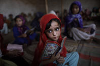 <p>Afghan refugee Aisha Daoud, 4, holds a copy of the Quran while taking part in a daily class to learn how to read verses of the Quran, at a mosque in a poor neighborhood of Rawalpindi, Pakistan, Oct. 19, 2010. (Photo: Muhammed Muheisen/AP) </p>