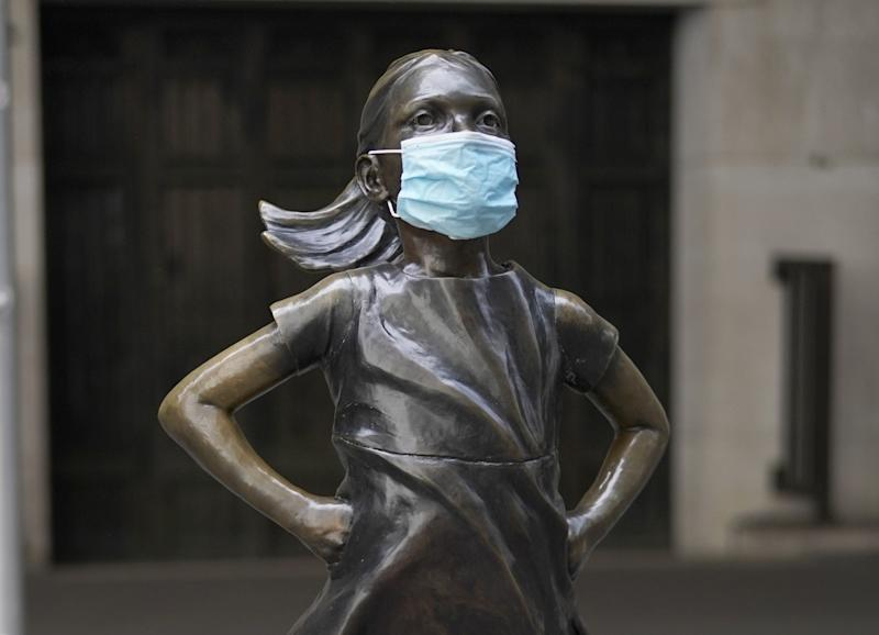 Fearless Girl, a bronze sculpture by Kristen Visbalthe, with a PPE mask on in front of the New York Stock Exchange in the Wall Street Financial District of Manhattan New York May 19, 2020. (Photo by TIMOTHY A. CLARY / AFP) / RESTRICTED TO EDITORIAL USE - MANDATORY MENTION OF THE ARTIST UPON PUBLICATION - TO ILLUSTRATE THE EVENT AS SPECIFIED IN THE CAPTION (Photo by TIMOTHY A. CLARY/AFP via Getty Images)