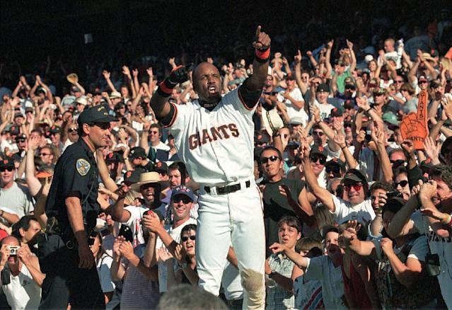 FILE - San Francisco Giants' Barry Bonds celebrates on top of the Giants dugout after they beat the San Diego Padres to win the National League West title in San Francisco, Saturday Sept. 27, 1997. The Giants won the game, 6-1, and won their first playoff berth since 1989. Candlestick Park, known for its bone-numbing winds, the Catch and the earthquake-rocked 1989 World Series is officially closing after more than a half century of hosting sporting and cultural events. In a bow to historical symmetry, the Stick's finale will be a performance Thursday by Paul McCartney, 48 years after the Beatles' last scheduled concert lit up the venue. (AP Photo/Eric Risberg)