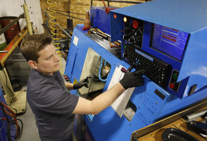 In this Monday Nov. 11, 2019, Kyle Chittock sets up a computerized lathe at his family's manufacturing business, Simple Country, in Grass Valley, Calif. Power outages, implemented by Pacific Gas & Electric in hopes of preventing wildfires have been unpredictable and making it hard for companies to operate. Because power could be turned off or on at any time, Chittock couldn't know in advance whether to tell staffers to come in or start home.(AP Photo/Rich Pedroncelli)