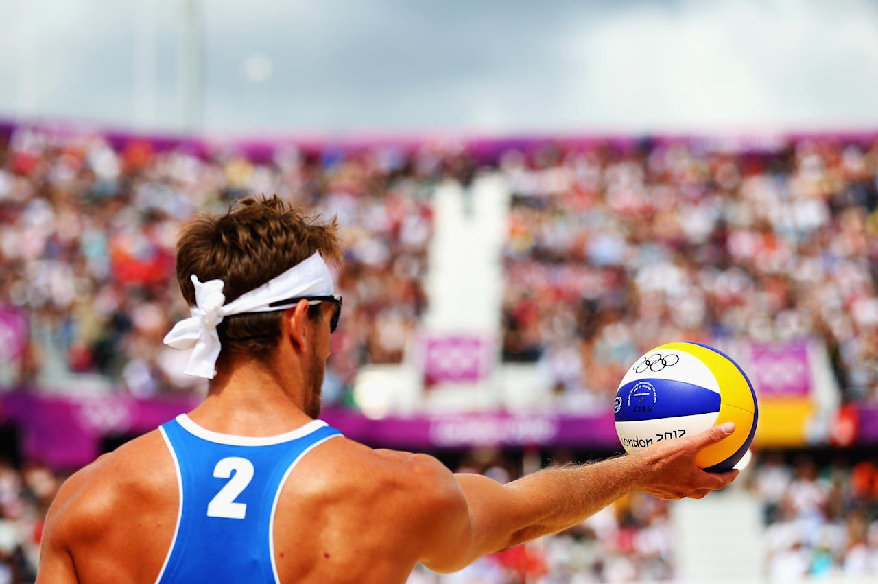 LONDON, ENGLAND - JULY 30:  Martin Reader of Canada prepares to serve during the Men's Beach Volleyball Preliminary match between Norway and Canada on Day 3 of the London 2012 Olympic Games at Horse Guards Parade on July 30, 2012 in London, England.  (Photo by Ryan Pierse/Getty Images)