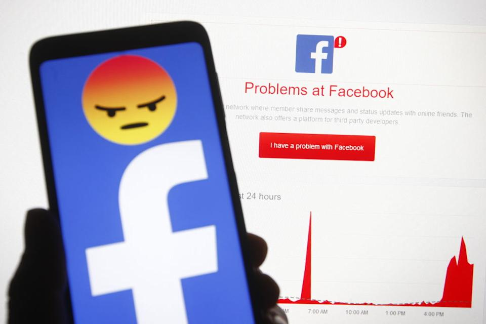 In this photo illustration a Facebook logo is seen on a smartphone screen in front of words 'Problems at Facebook' and a graphic which displayed on Downdetector website.