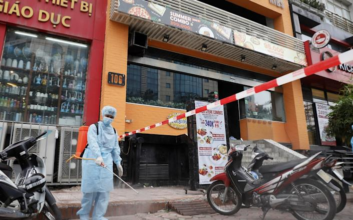 Mandatory Credit: Photo by LUONG THAI LINH/EPA-EFE/Shutterstock (10726328c) A worker sprays disinfectant next to a restaurant where a worker tested positive with COVID-19 after travel from Da Nang, in Hanoi, Vietnam 29 July 2020. Covid-19 outbreak in Vietnam, Ha Noi, Viet Nam - 29 Jul 2020 - Shutterstock