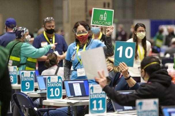 PHOTO: Staff and volunteers work vaccination stations during opening day of the Community Vaccination Site at the Lumen Field Event Center in Seattle, March 13, 2021. (Jason Redmond/AFP via Getty Images)