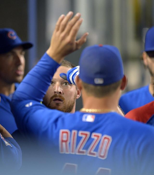 Chicago Cubs' Travis Wood, left, is congratulated by Anthony Rizzo after scoring on a single by Dioner Navarro during the third inning of a baseball game against the Los Angeles Dodgers, Tuesday, Aug. 27, 2013, in Los Angeles. (AP Photo/Mark J. Terrill)