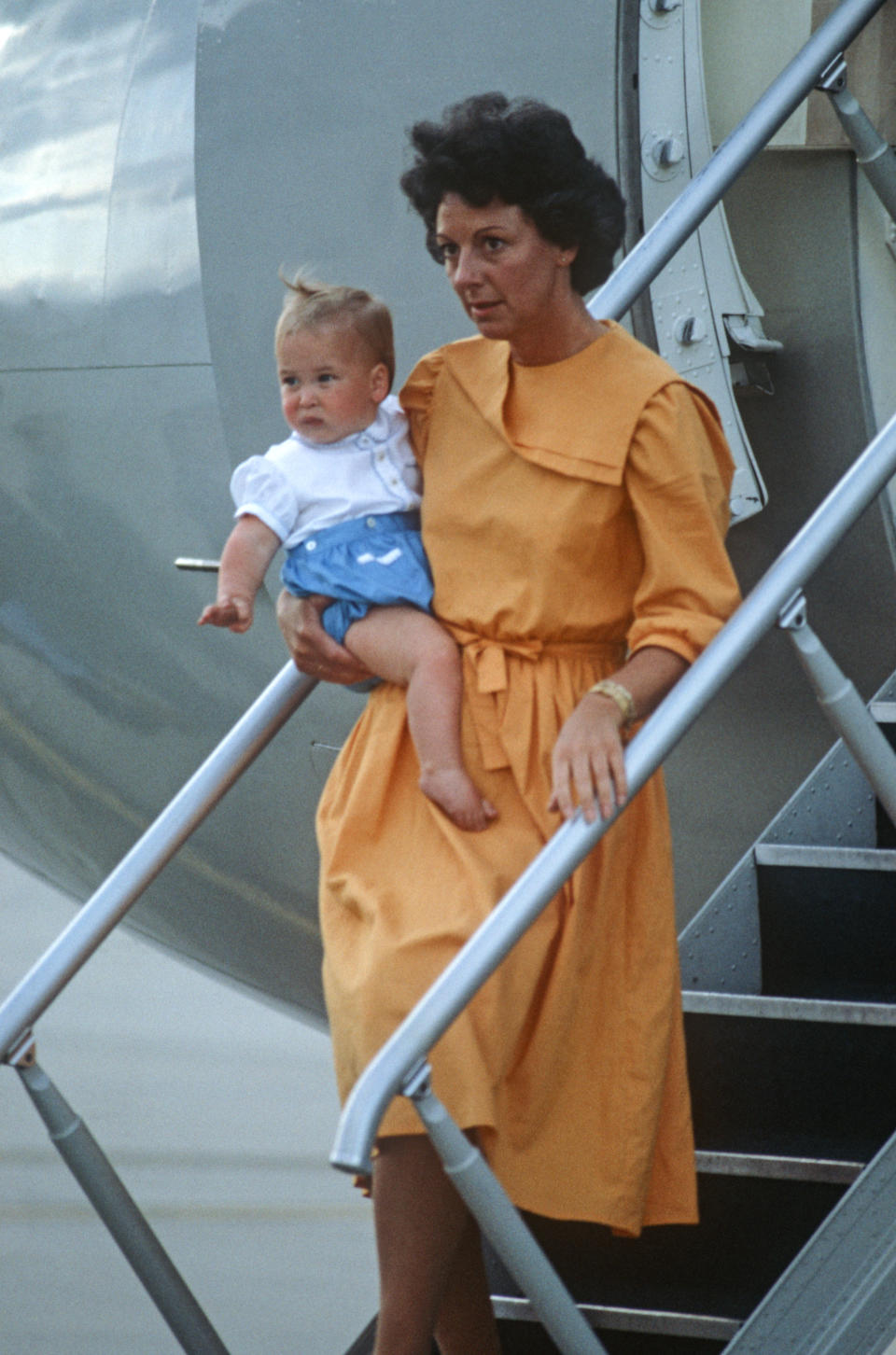 Nanny Barbara Barnes carries Prince William off a plane at Melbourne Airport, Australia, in 1983. (David Levenson/Getty Images)