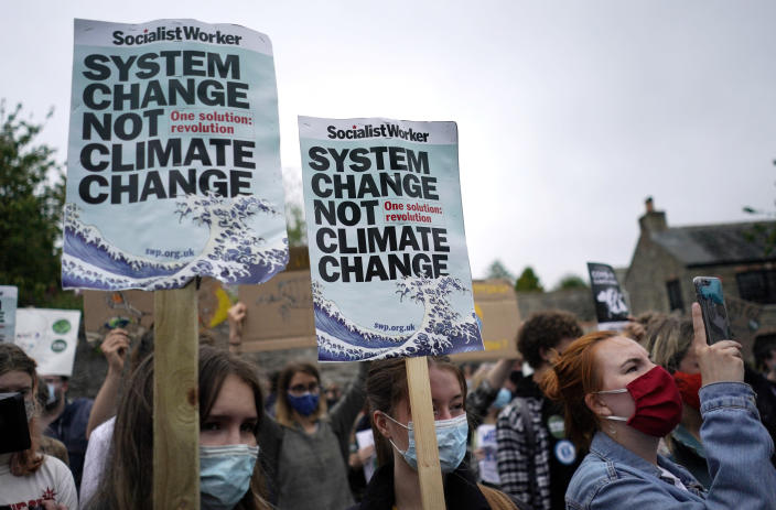 Climate activists wave signs and chant as they march during a demonstration taking place outside a meeting of G7 leaders in Falmouth, Cornwall, England, Friday, June 11, 2021. Leaders of the G7 begin their first of three days of meetings on Friday in Carbis Bay, in which they will discuss COVID-19, climate, foreign policy and the economy. (AP Photo/Alberto Pezzali)