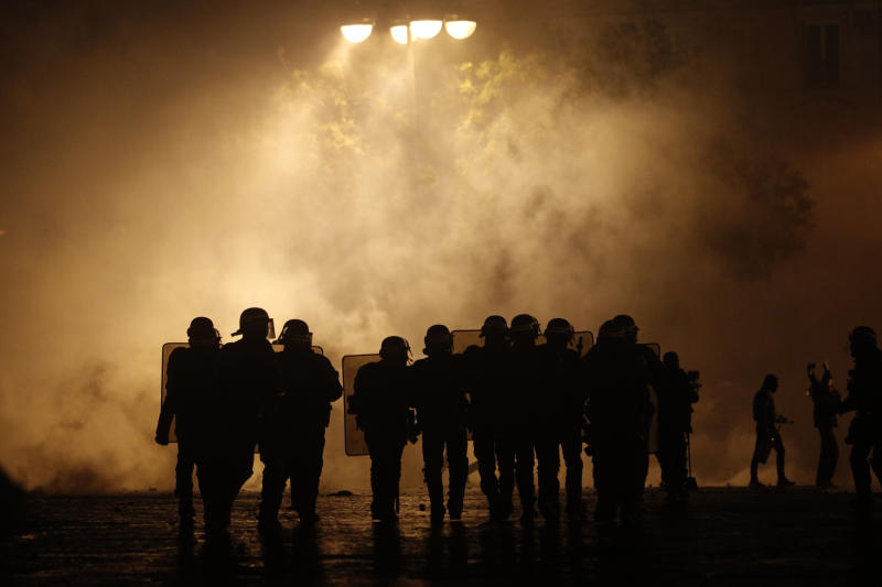 Riot police officers take position near the Arc de Triomphe, Saturday, Dec.1, 2018 in Paris. A French protest against rising taxes and the high cost of living turned into a riot Saturday in Paris as police fired tear gas and water cannon in street battles with activists wearing the fluorescent yellow vests of a new movement. (AP Photo/Kamil Zihnioglu)