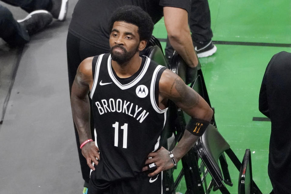 FILE - Brooklyn Nets guard Kyrie Irving looks up at the fans at TD Garden after they defeated the Boston Celtics in Game 4 during an NBA basketball first-round playoff series in Boston, in this Sunday, May 30, 2021, file photo. The Brooklyn Nets won't play Kyrie Irving until he can play in all their games, unwilling to let questions about his vaccination status linger into the season. The Nets announced Tuesday, Oct. 12, 2021, that Irving would not play or practice with them until he could be a full participant, ending the idea that he would play in only road games. Without mentioning his vaccination status, general manager Sean Marks said Irving has made a decision that keeps him from being able to perform with the team. (AP Photo/Elise Amendola, File)