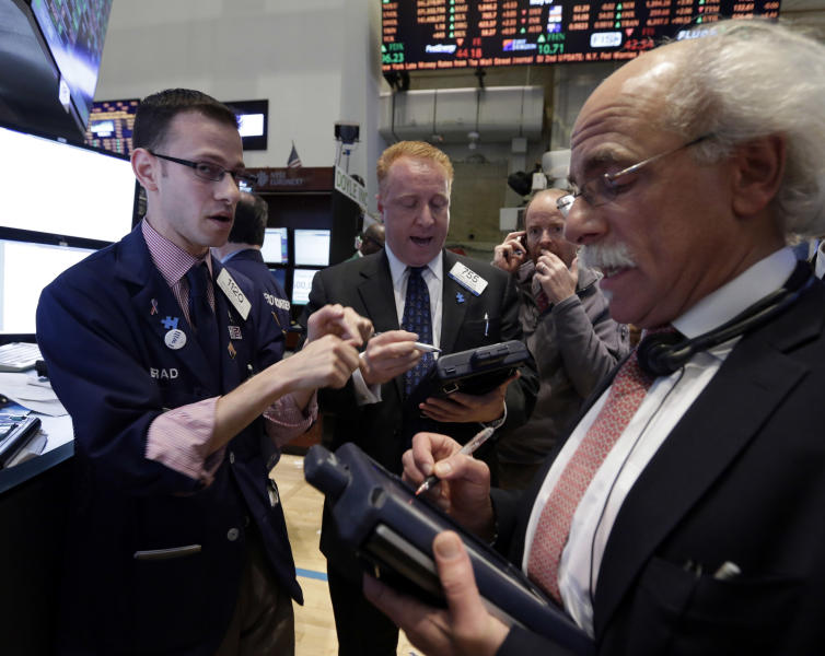 Specialist Bradley Kessler, lewft, works with traders on the floor of the New York Stock Exchange Tuesday, May 7, 2013. The Dow Jones industrial average punched through another milestone Tuesday: its first close above 15,000. (AP Photo/Richard Drew)