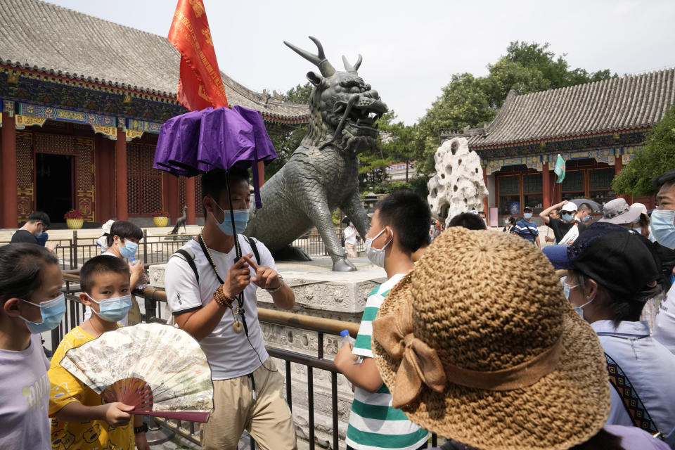 A tour guide leads a group of domestic tourists visiting the Summer Palace in Beijing on Aug. 3, 2021. Strict virus control measures have allowed China to return to relatively normal life. The number of tourists visiting Beijing in June and July tripled compared to the same period last year, while revenue quadrupled, according to Trip.com, China's largest online travel booking platform. (AP Photo/Ng Han Guan)