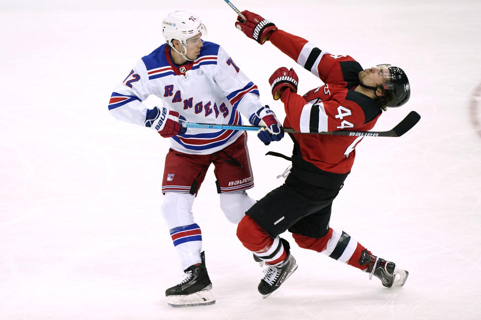 New York Rangers center Filip Chytil (72) uses his stick to fend off New Jersey Devils left wing Miles Wood (44) during the first period of an NHL hockey game, Thursday, March 4, 2021, in Newark, N.J. Chytull was penalized for the play. (AP Photo/Kathy Willens)
