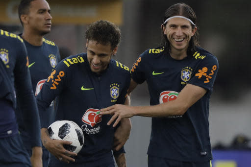 Brazil's Filipe Luis, right, embraces Neymar during a practice session of the Brazilian national soccer team ahead the World Cup in Russia, at the Granja Comary training center In Teresopolis, Brazil, Friday, May 25, 2018. (AP Photo/Leo Correa)