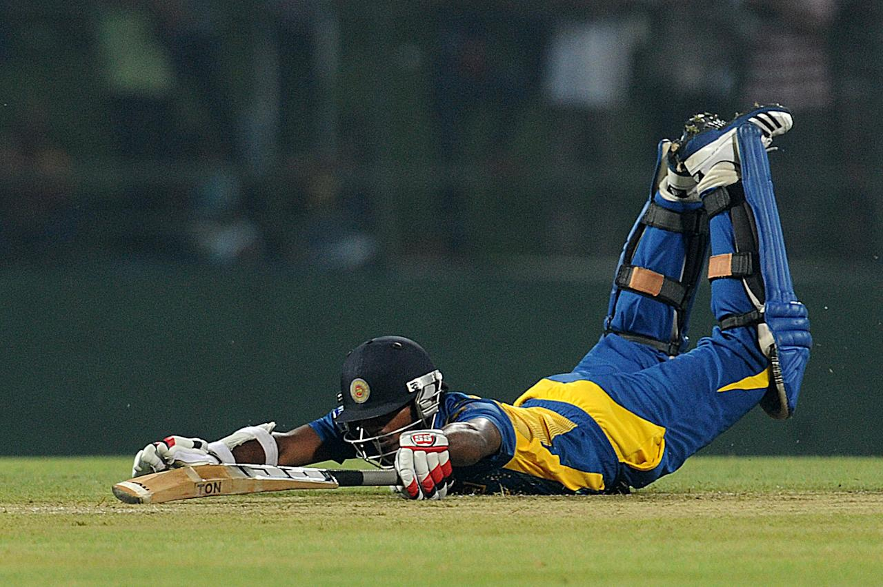 Sri Lankan cricketer Kusal Janith Perera dives for the wicket as he avoids a runout during the the Twenty20 International match between Sri Lanka and Bangladesh at The Pallekele International Cricket Stadium in Pallekele on March 31, 2013. AFP PHOTO/ Ishara S. KODIKARA