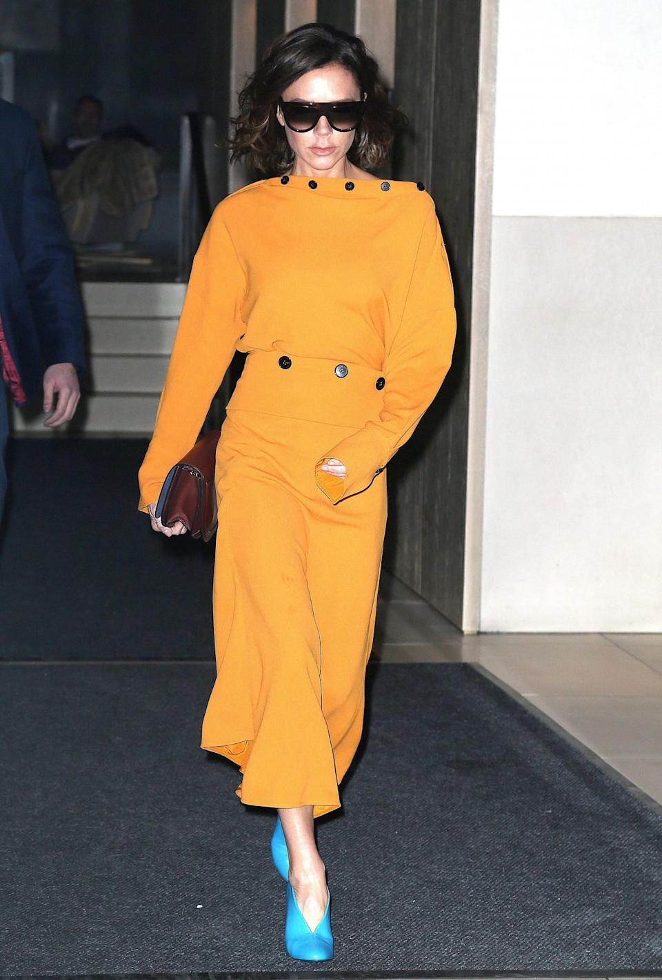 <p>This tangerine coloured dress was a bold look – especially paired with bright blue shoes. But, naturally, VB made it work for her. <em>[Photo: Rex]</em> </p>