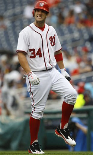Washington Nationals' Bryce Harper reacts to being hit by a foul tip in the first inning of the first baseball game of a doubleheader against the Atlanta Braves, Saturday, July 21, 2012, in Washington. (AP Photo/Carolyn Kaster)