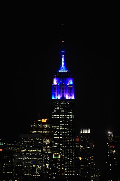 In this Nov. 26, 2012, photo provided by the Empire State Building, the top floors of New York's Empire State Building are lit in blue and white light after being switched on by R&B star Alicia Keys. The landmark boasts a new LED lighting system with a palette of more than 16 million colors in limitless combinations, including ripples, sparkles, chasers, sweeps, strobes and bursts. The old lights came in only 10 colors. (AP Photo/Empire State Building, Bryan Smith)