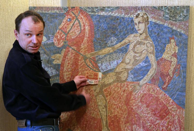 In this photo taken Friday, Feb. 8, 2013, Belarusian artist Igor Arinich shows an image made of hundreds of Soviet-era banknotes in Minsk, Belarus. Arinich has used Soviet banknotes which he buys at local flea markets in Belarus for his works. (AP Photo/Sergei Grits)