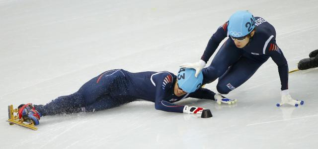 Sin Da-woon (L) and Lee Han-bin (R) of Korea crash out in the men's 1,500 metres short track speed skating semi-final event at the Iceberg Skating Palace during the 2014 Sochi Winter Olympics February 10, 2014. REUTERS/Brian Snyder (RUSSIA - Tags: SPORT SPEED SKATING OLYMPICS)