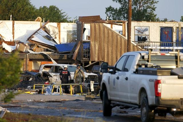 Workers look through tornado damage at the American Budget Value Inn in El Reno