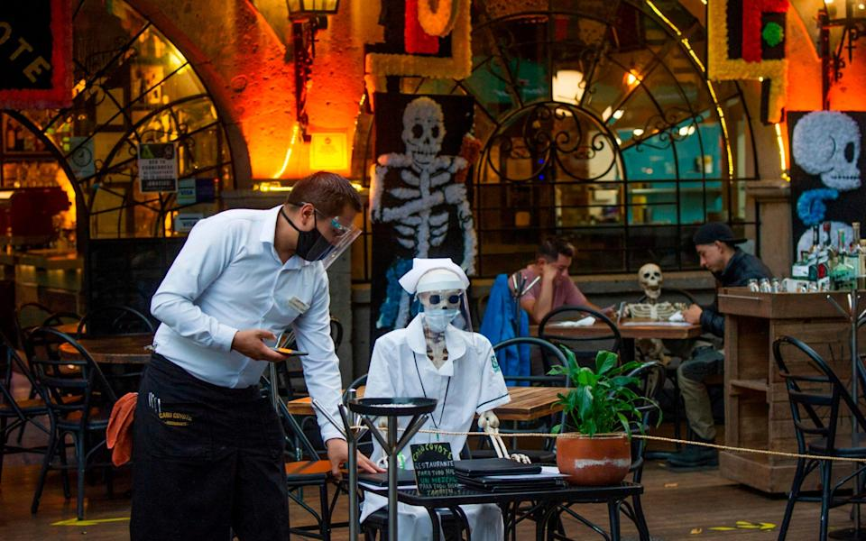 View of a so-called Calaca ,commonly used for decoration during the Mexican Day of the Dead, is used to keep social distancing measures at a restaurant in Coyoacan - AFP