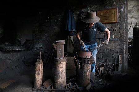 A blacksmith hammers a wok at a workshop for handmade woks in Datian village, Hubei province, China August 13, 2018. Picture taken August 13, 2018. REUTERS/Thomas Suen