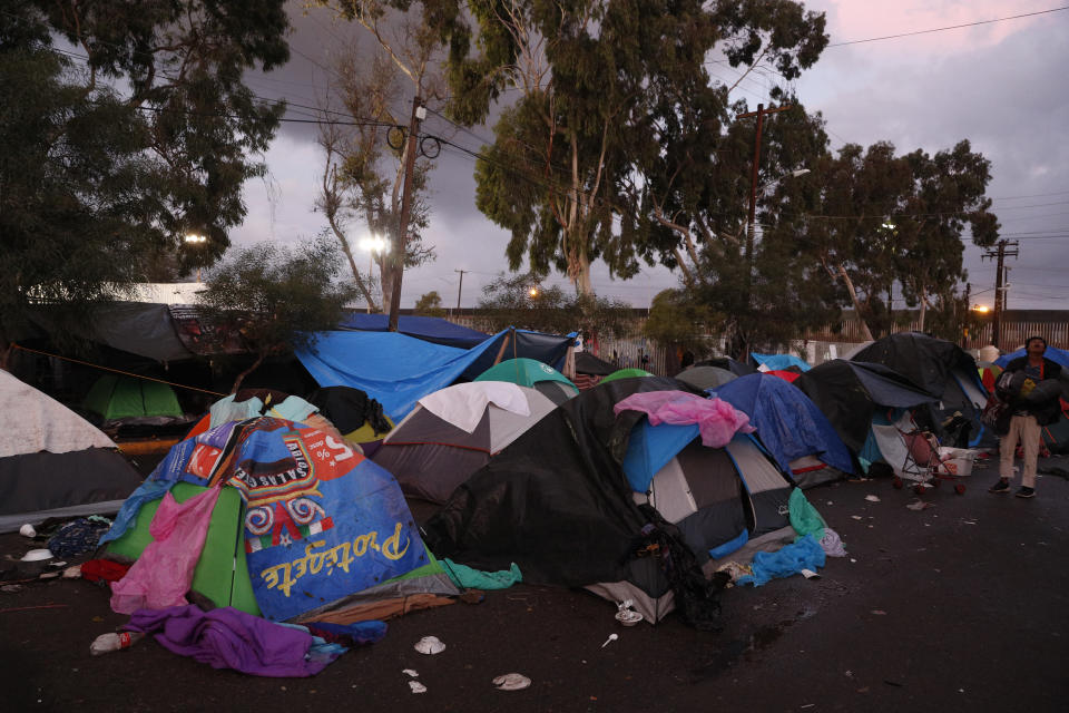People sleep in tents on a wet street as dawn breaks, outside the Benito Juarez sports complex where thousands of migrants were camping out, in Tijuana, Mexico, Friday, Nov. 30, 2018. Authorities in the Mexican city of Tijuana have begun moving some of more than 6,000 Central American migrants from an overcrowded shelter on the border to an events hall further away.(AP Photo/Rebecca Blackwell)